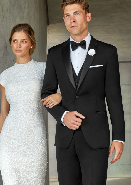 This photo of a groom shows a classic black tuxedo, evidenced by the satin on the lapel and the pockets. It also has fabric covered buttons making it a bit more formal. This tuxedo has a notch lapel, however tuxedos can also have jackets with a peak lapel and a shawl lapel as well.