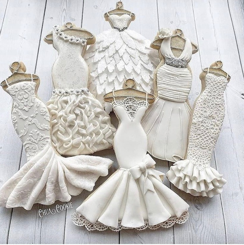 Sugar cookies shaped as mannequin forms iced in white looking like actual lace and silk wedding dresses