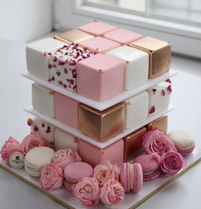 New twist on a dessert cake, bite size squares in pink and gold stacked up amid pink an white macaroons and roses