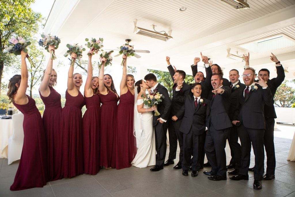 Bride and groom celebrate with a kiss surrounded by their whole party, maids in wine color and men in black tuxedos