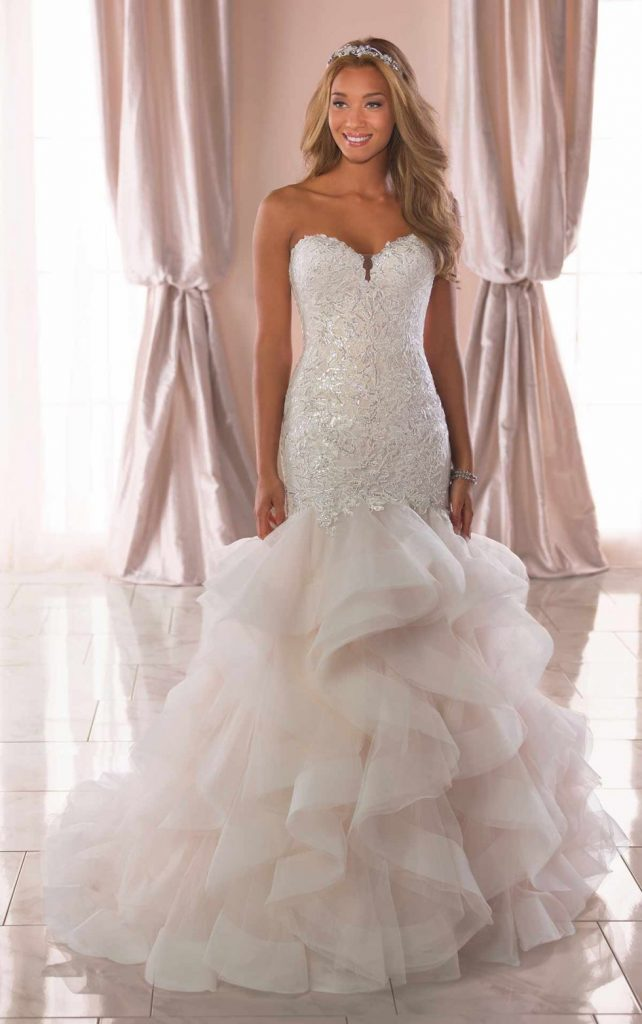 This wedding dress by designer Stella York is a mermaid dress with an organza tiered skirt.  This is a very fitted and ornate top with a full and fluffy skirt.