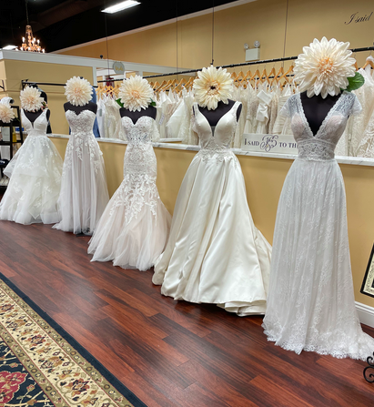 A row of 5 different wedding dresses all with different fabrics