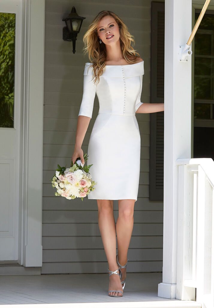 This picture shows a bride in a short plain crêpe dress, knee length, with a jacket that has three-quarter sleeves and buttons down the front.