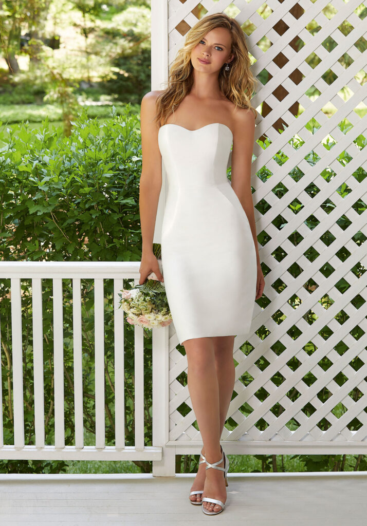 Photo shows plain white form fitting dress, strapless with a sweetheart neckline, cocktail length to the knee. Dress comes with a jacket that transforms the look to a classic, demure statement.