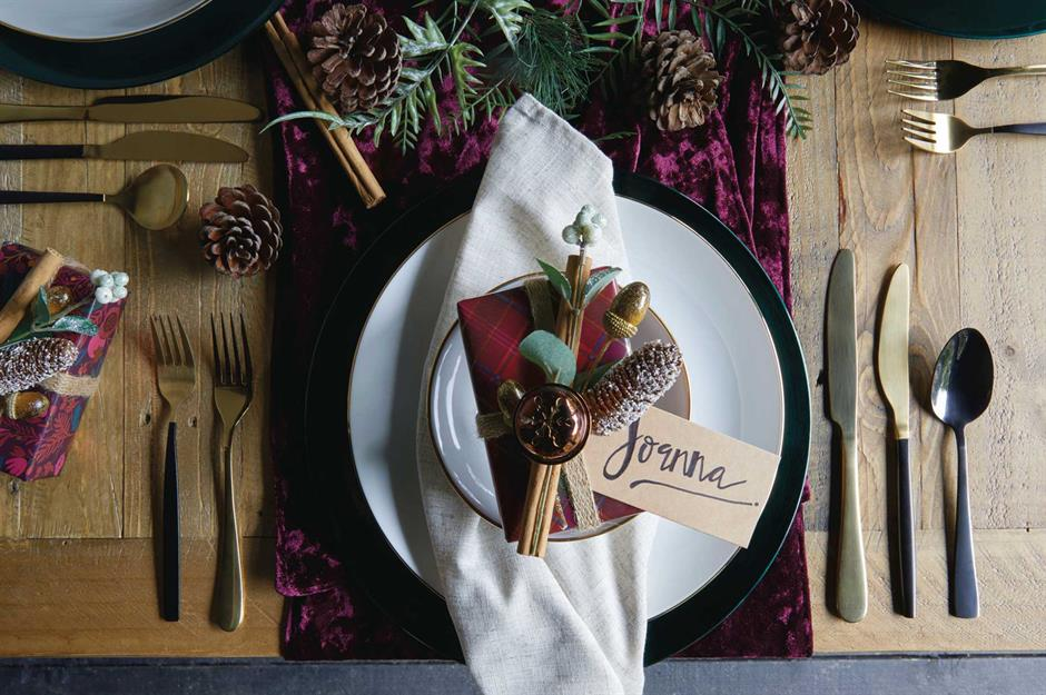 A beautiful autumn placesetting with plums, greenery, pinecones, and cinnamon sticks. Gold flatwear and gold-edged white china plates. When planning a micro wedding with fewer guests, placesettings of a more luxurious form are doable!