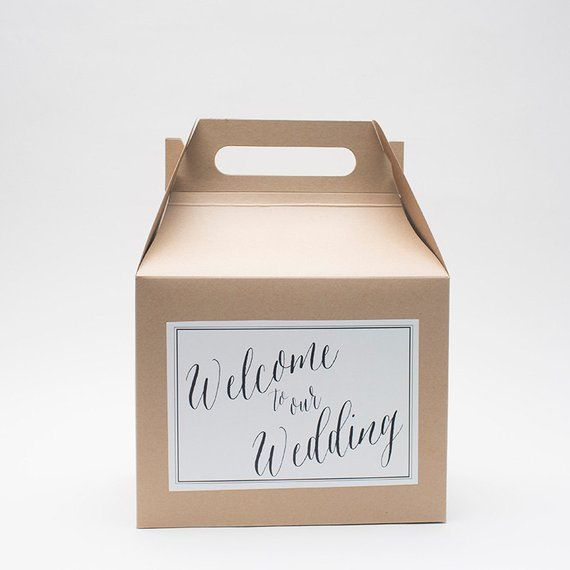 Cardboard wedding box with a handle, and a label saying welcome to our wedding in calligraphy.