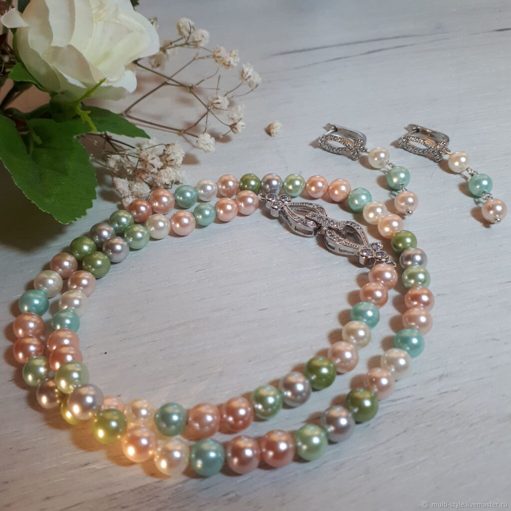 Photo shows a strand of pearls that are multi colored, mainly pastel, but include pink light blue lemon, and sage green. Also shown are a matching pair of drop earrings