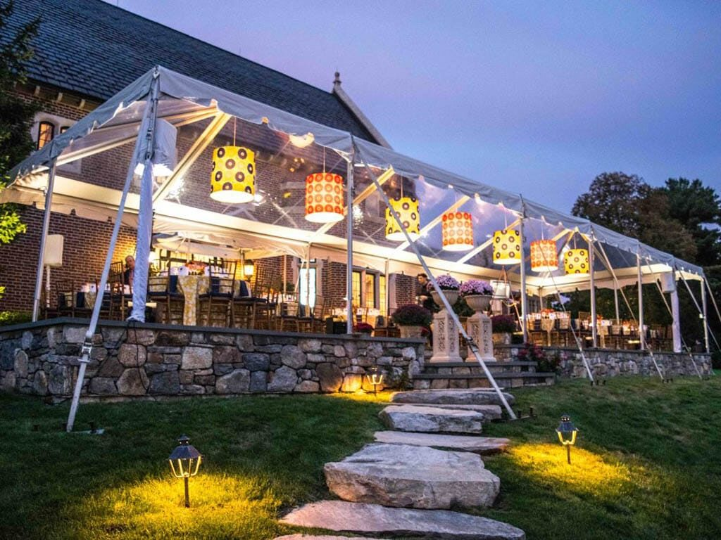 Tent installed over stone patio with pendant lights lining the edge, lighting has cylindar shaped yellow shades in alternating patterns of blue and orange and navy blue flowers