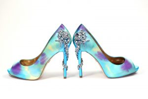 Photo is a pair of light blue high-heeled wedding shoes that have beading on the back and wrapped around the heel, and dyed purple and yellow to match the wedding colors.
