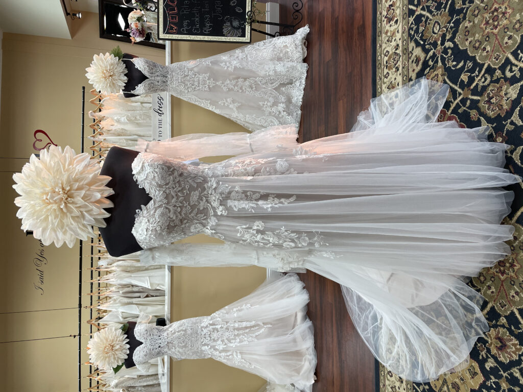 A-line wedding dress with a sweetheart neckline, lace bodice with applique flowing down into light tulle skirt, and detachable sleeves