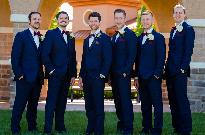 Our groom and his five groomsmen wearing the navy colored Sebastian tuxedo by Ike Behar. The groom differentiated himself by wearing a bowtie in a wine color with a floral pattern and matching pocket square, while his groomsmen wore a solid wine color bowtie and pocket square. He also had a Calla lily boutonniere while his groomsmen had carnations.