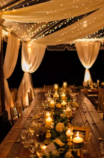 Outdoor evening wedding with string lights, tented canopy with tie back curtain drops, long picnic tables allowing for distance between guests, and beautiful greenery and candles lining the center from end to end