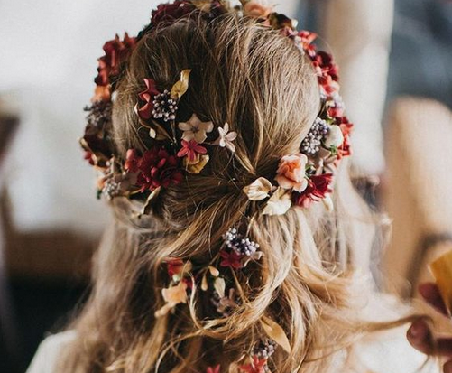 Photo shows berry and peach colored flowers woven into brides hair