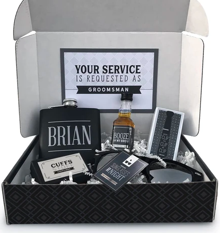 """Black box with a personalized flask, whiskey, cufflinks, sunglasses, and a tie clip, asking """"Will you be my groomsman?"""""""