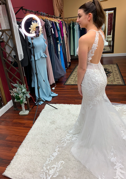 Bride in a mermaid lace wedding dress with a keyhole back using a ring light to share the dress details over the phone with her family who participated in the video appointment from home