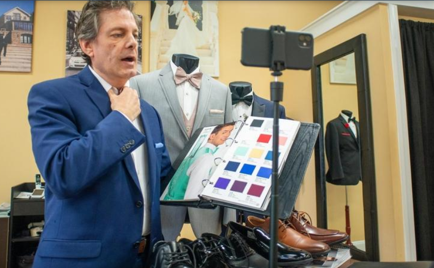 """Co-owner of Darianna Bridal & Tuxedo Franco Salerno holds a swatch color book to a video tuxedo appointment, while also displaying  black and brown shoe selections and a gray Michael Kors tuxedo called """"Chrome""""."""
