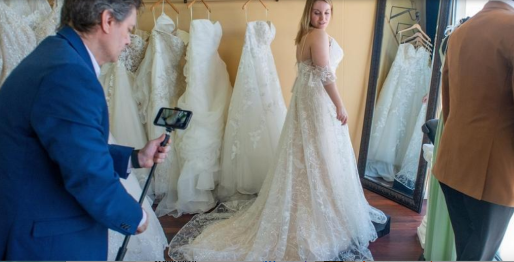 Darianna Bridal & Tuxedo manager Daria Capaldi video models an off-the-shoulder, lace wedding dress with a chapel length train in preparation for an online bridal video appointment
