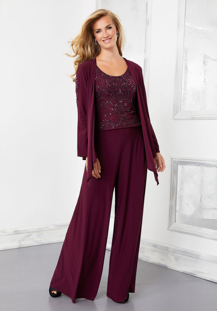 A three-piece women's pants suit in the color wine on a model including chiffon pants, beaded tank top, and matching chiffon long sleeve buttonless jacket