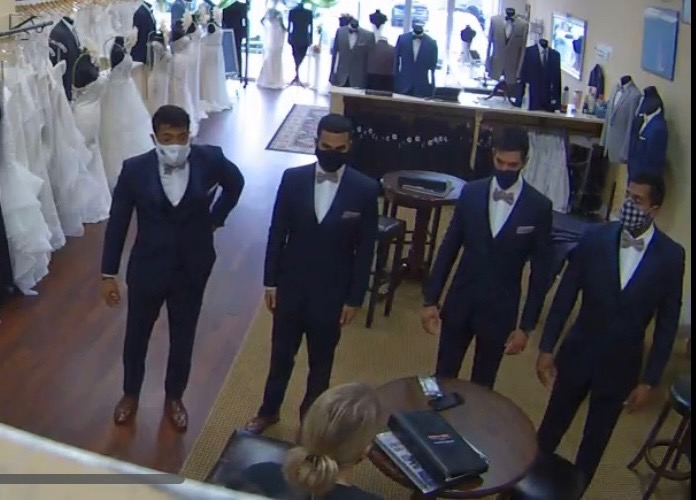 Four groomsmen in Ike Behar navy tuxedos with rose colored bowties are inspected by a Darianna Bridal & Tuxedo staff member. She is making sure they all fit perfectly before they attend the event. A benefit when you rent with us.