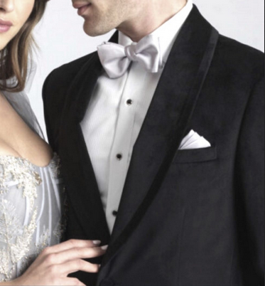 Black tuxedo with a thick shawl lapel and satin stripe, white shirt, bowtie, and pocket square
