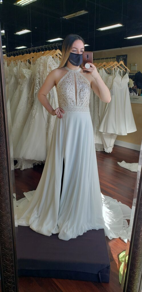 Bride wearing a cut in halter neck line wedding dress with full lace bodice, accentuated waist, and lined chiffon skirt with a slit. Micro wedding dress, destination wedding dress, Morilee, Brandy wedding dress