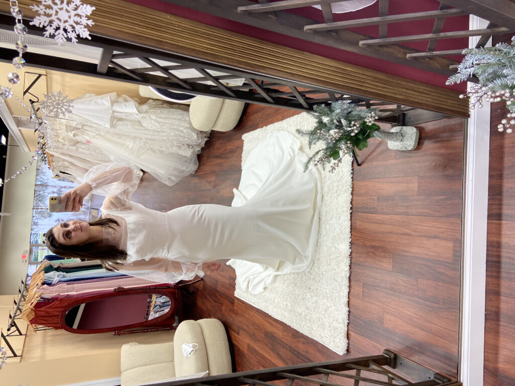 Bride modeling the Aiden dress, Madi Lane, crepe wedding dress, square neck, tank strap, sheer jacket over lay with pearls, micro wedding dress