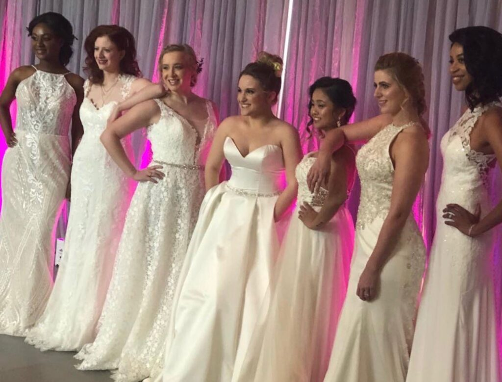 Seven Darianna Bridal & Tuxedo bridal models in various silhouettes of wedding dresses, in fabrics of lace, satin, English net, and crepe, are lined up and ready to walk the runway in a fashion show.