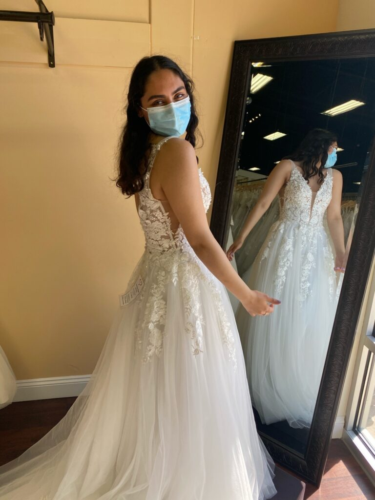 Bride looking over her shoulder wearing an A-line wedding dress made of lace on the top and a tulle layered skirt