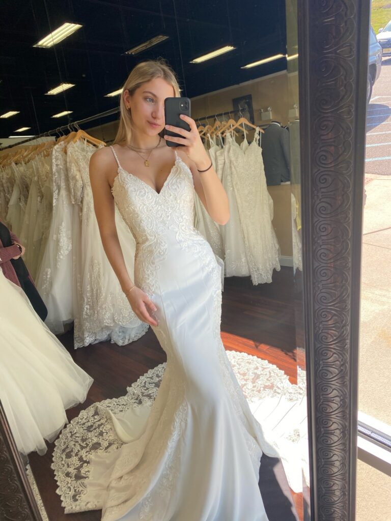 Bride taking a selfie in the mirror wearing a perfectly fitted mermaid dress made of crêpe and lace with a V-neck and beaded straps, and a gorgeous lace train