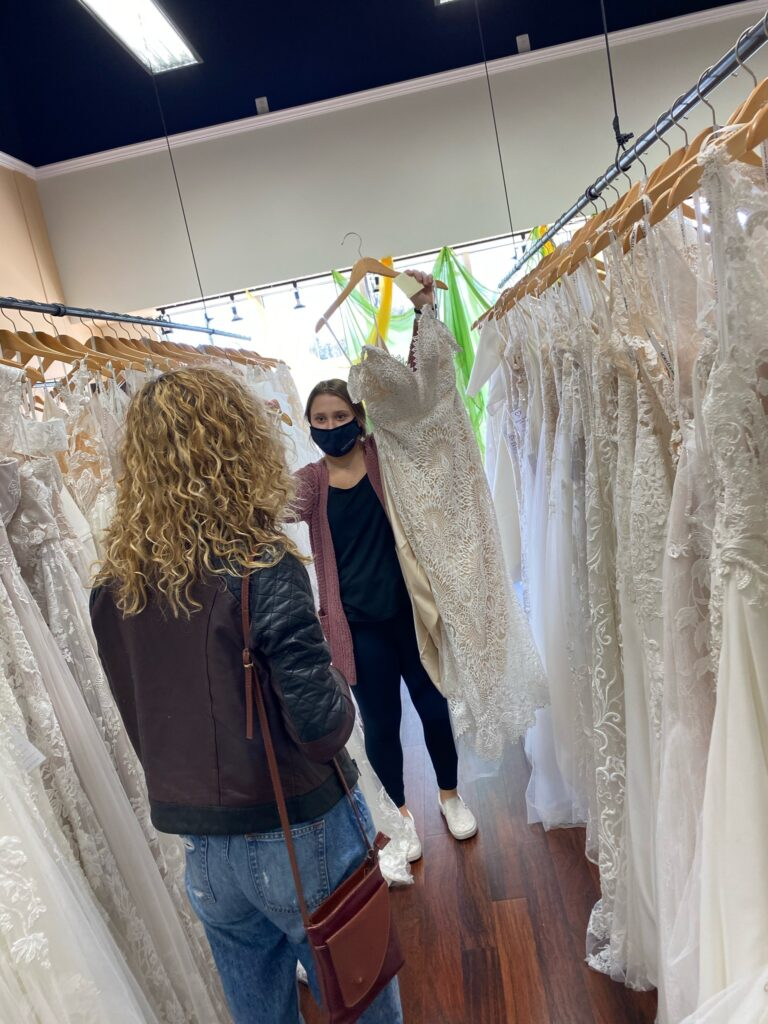 Bridal stylist Tori chooses a lace fit and flare wedding dress from the gallery of dresses for Val to try on