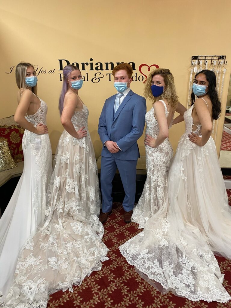 Groom in a cornflower blue color tuxedo and four bridal models looking over their shoulder in lace dresses both fitted and Eileen