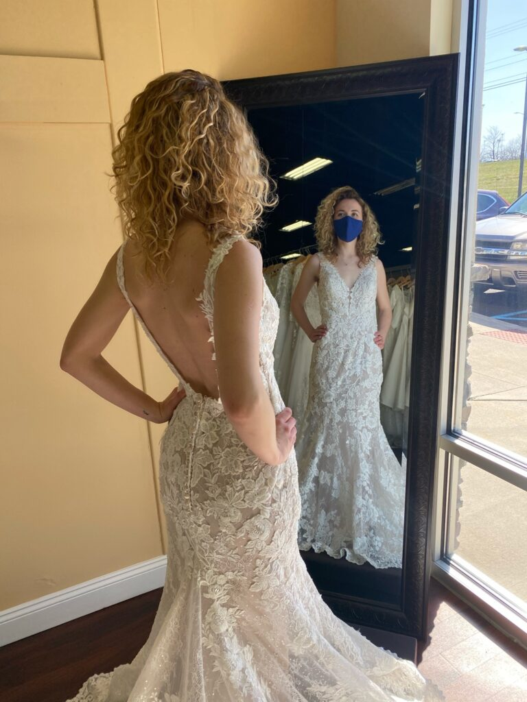 Bride in a full lace fit and flare V-neck dress with a low back having photo taken in the mirror