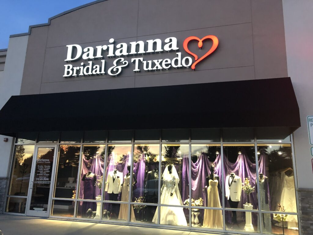 Store front of Darianna Bridal & Tuxedo with wedding dresses and tuxedo mannequins in the window, purple curtains, flowers, white tuxedos lit up at night time. Ready to say yes to the dress!