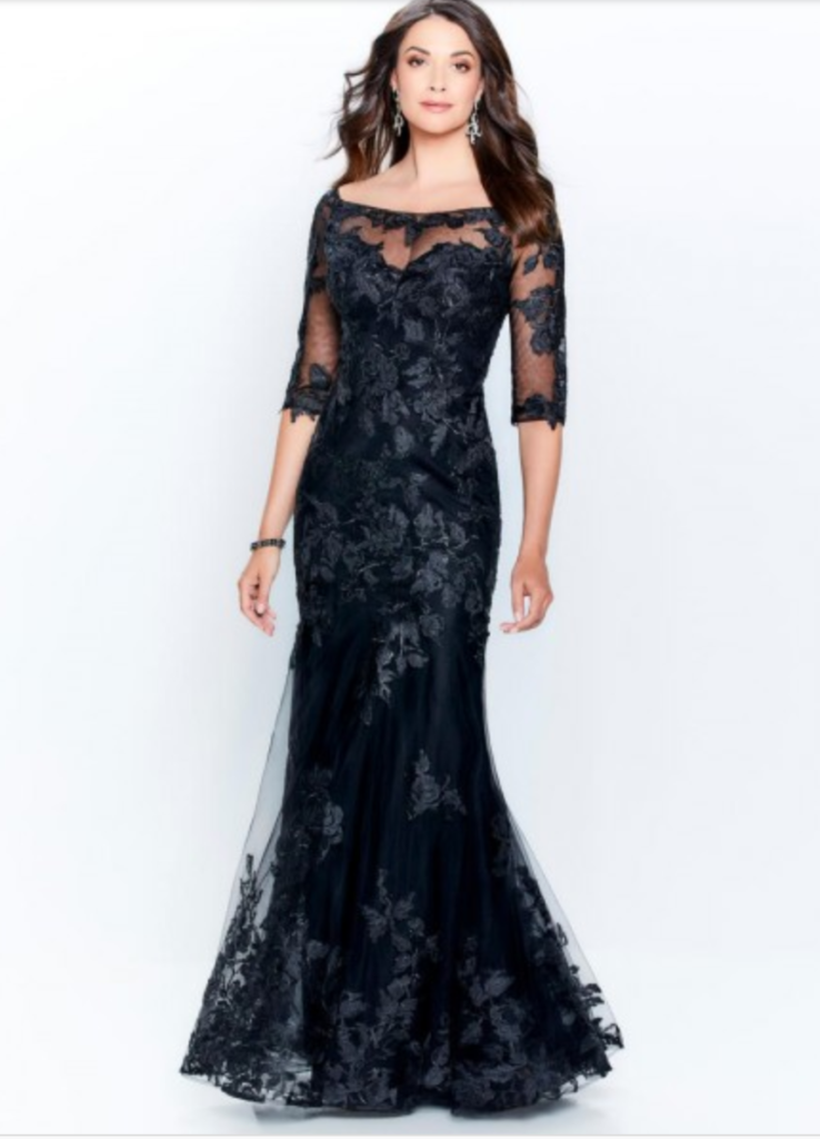 Mother of the bride dress from Mon Cheri Montage line with an off the shoulder neck line, three-quarter inch sleeves and all over lace appliqué, shown in black comes in delphinium as well