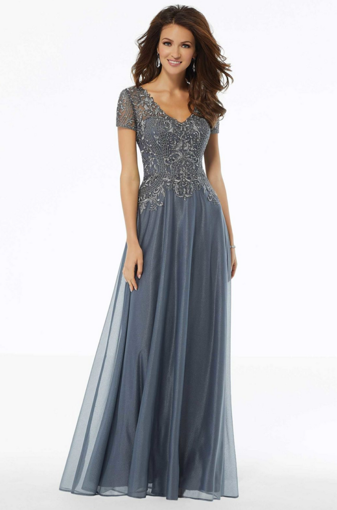 Beautiful mother of the bride dress in a slate blue color with beaded short sleeves, V-neck line, fitted bodice into dropped waste slim a-line.