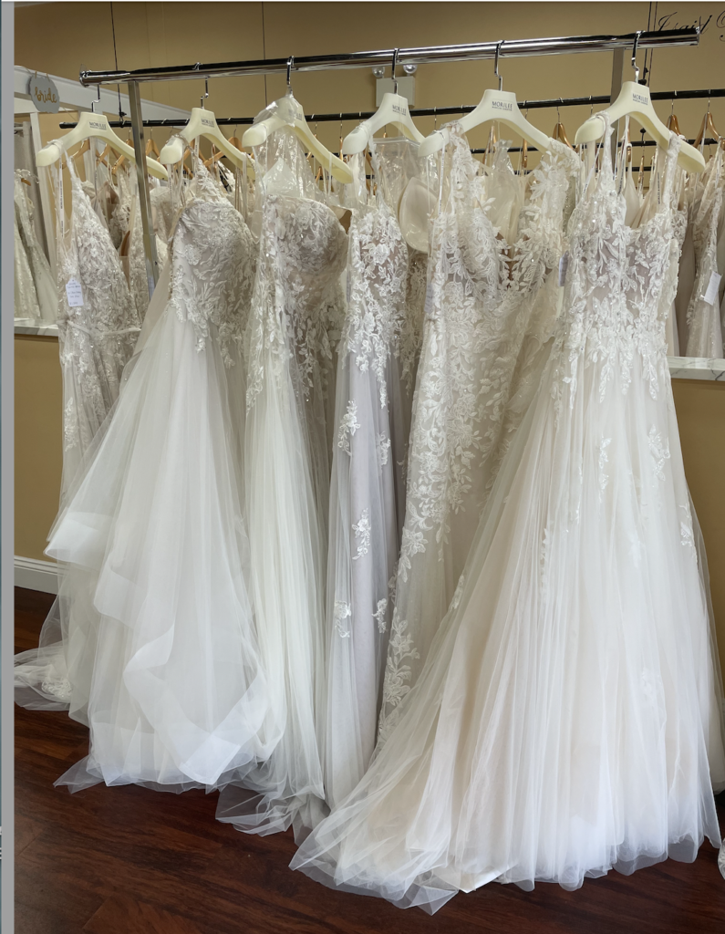Opening and displaying trunk show wedding dresses from designer Morilee with lace and tulle in ivory and blush colors